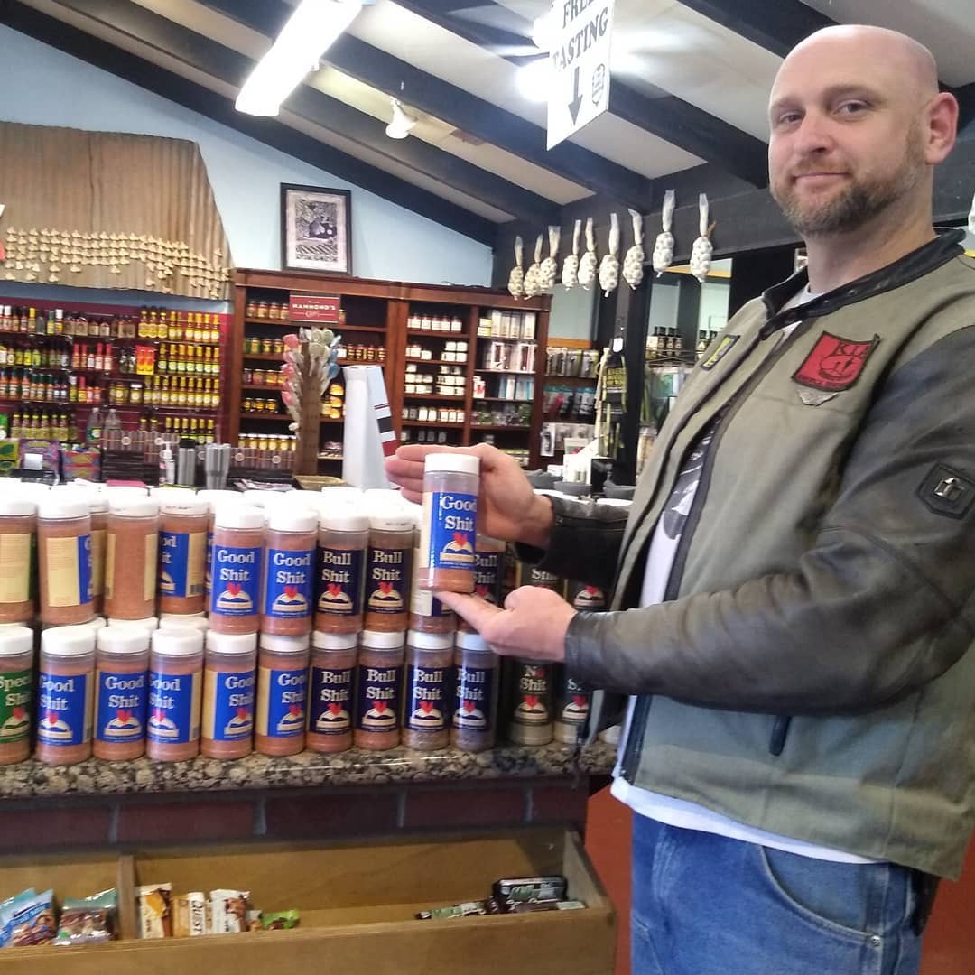 person holding a can of seasoning in a store
