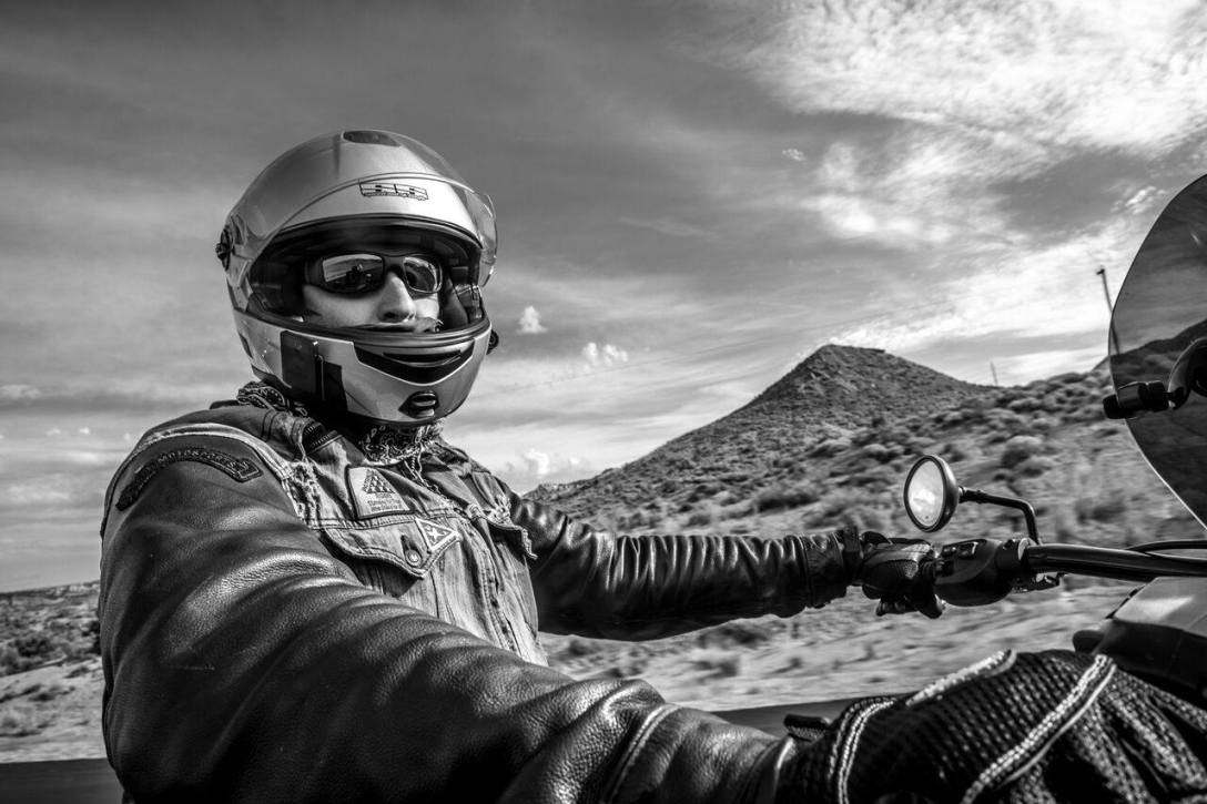 motorcycle rider in desert with helmet leather jacket
