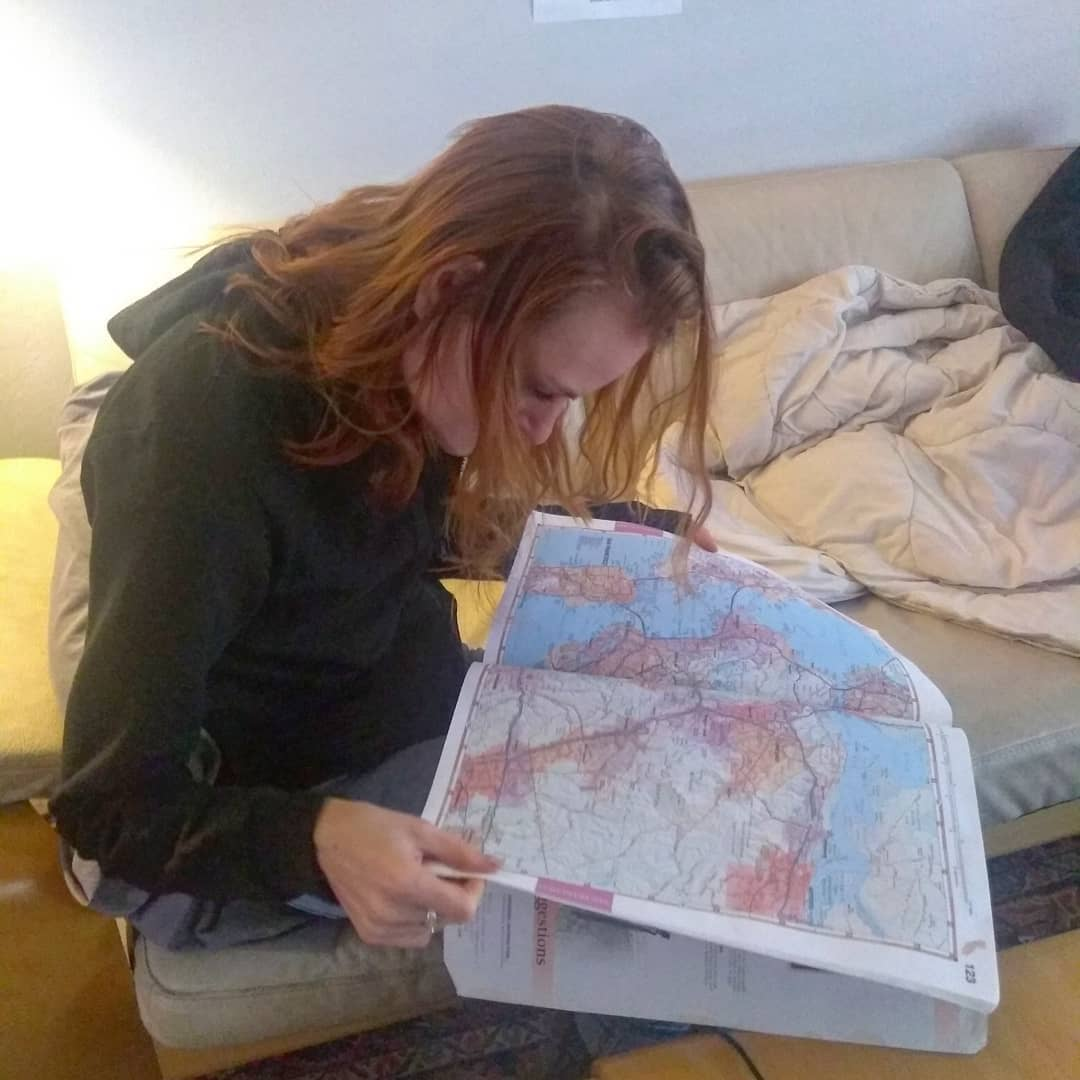 Kate reading map road atlas, woman.