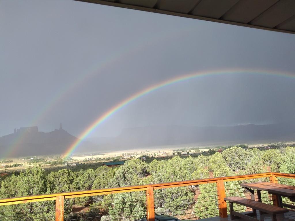 rainbow on horizon in desert mountain rain storm