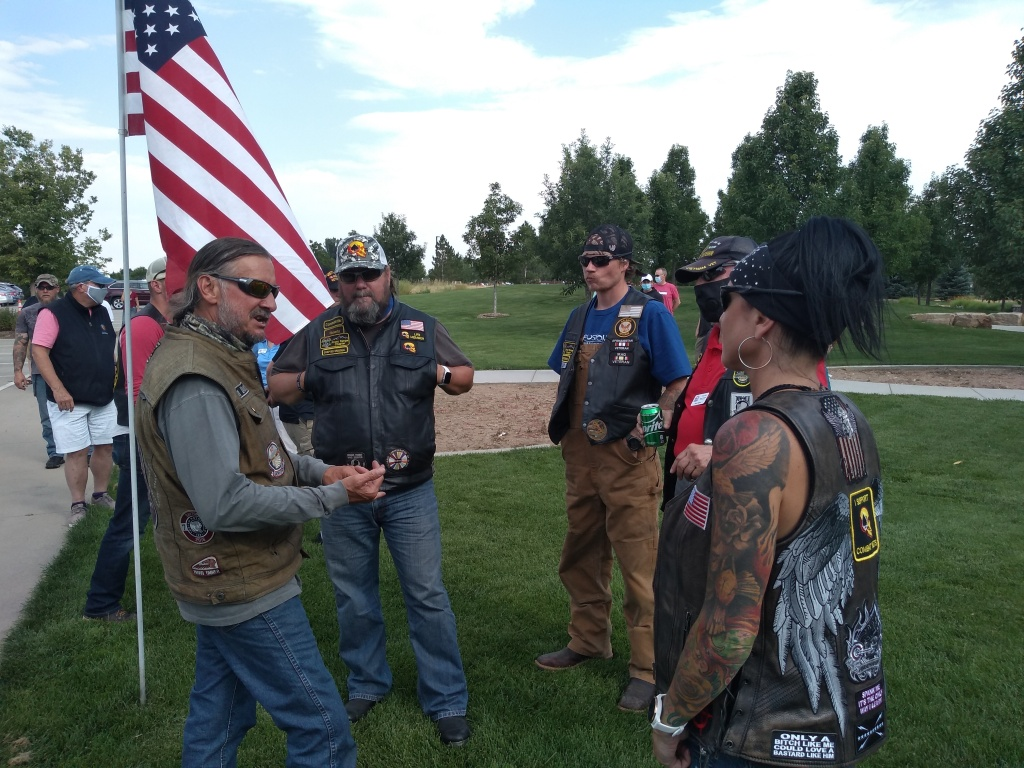 motorcylists stand in a park near a flag