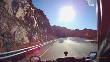motorcycle pov on highway in mountains with sun